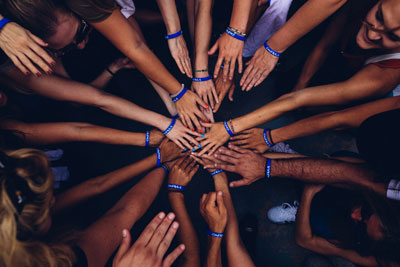 photo of a group placing their hands in a circle to show support